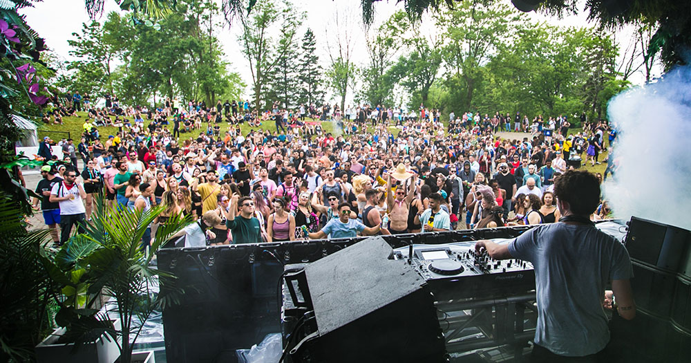 A DJ playing on stage at a music festival a crowd dancing in front