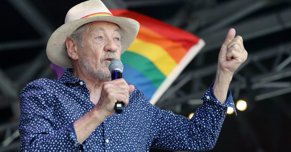 Ian McKellen speaks in microphone in front of rainbow flag