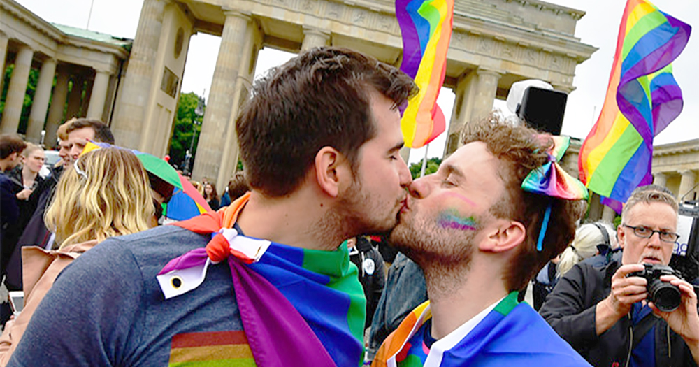 Two men wearing rainbow flags kiss in celebration of civil unions passing in Italy