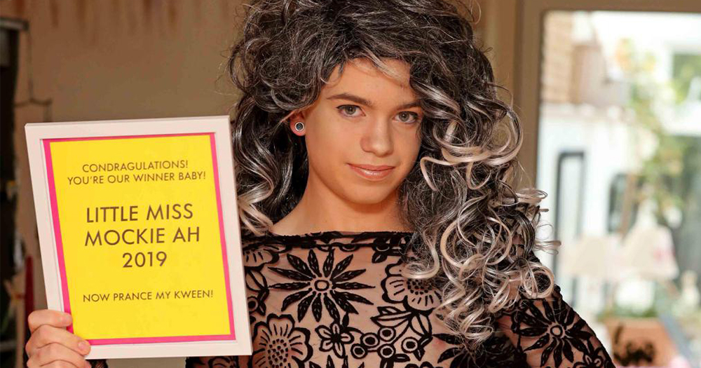 14 year old drag queen in lace top and black and grey wig holding up plaque which says