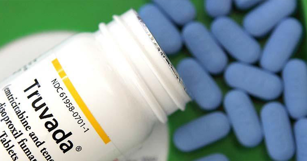 blue PrEP pills and bottle that reads 'Truvada' sits on table