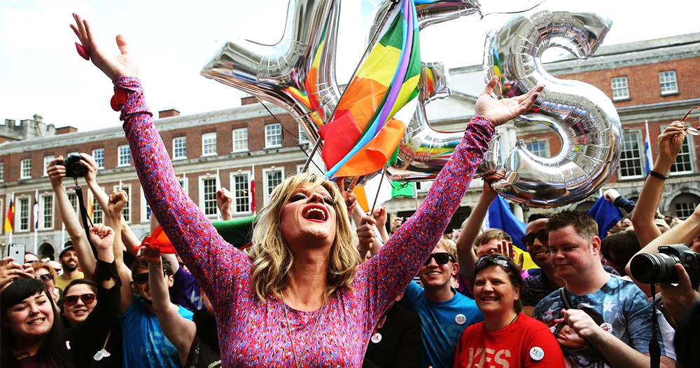 Drag queen Panti throws her hands in the air surrounded by rainbow coloured clad people