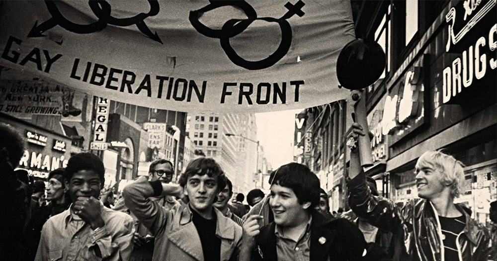 Scene from a 50th anniversary of Stonewall documentary featuring people marching holding a 'gay liberation front' sign