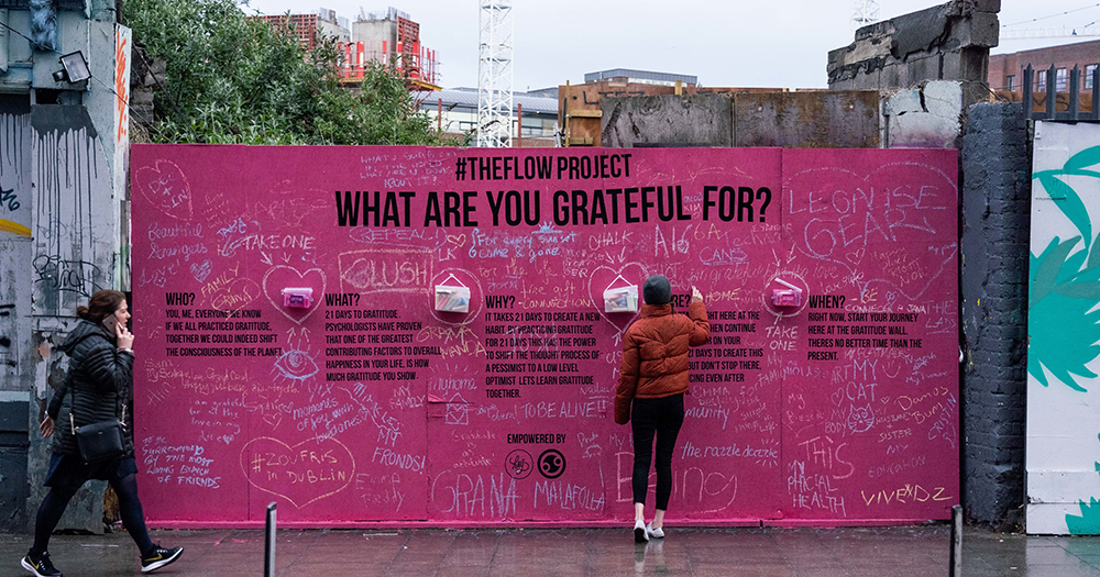 pink chalk board on Dublin street with girl writing gratitude message