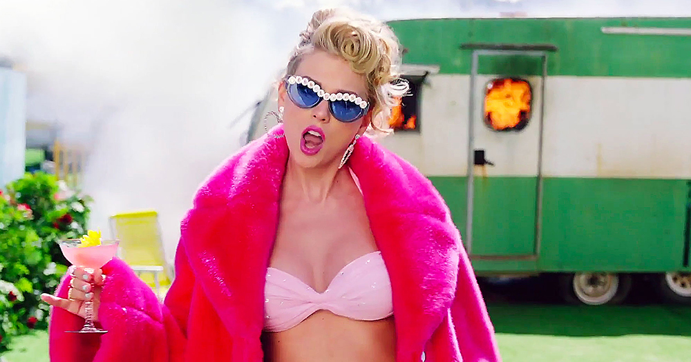 taylor swift stands in front of green trailer in pink fur and sunglasses
