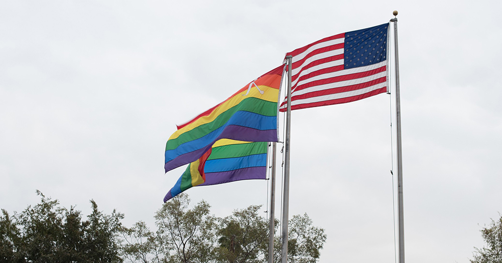 american flag and pride flag flying on flag poles