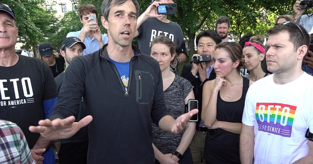 "Beto O'rourke stands among supporters while speaking...one supporter wears a rainbow shirt that reads ""beto"""