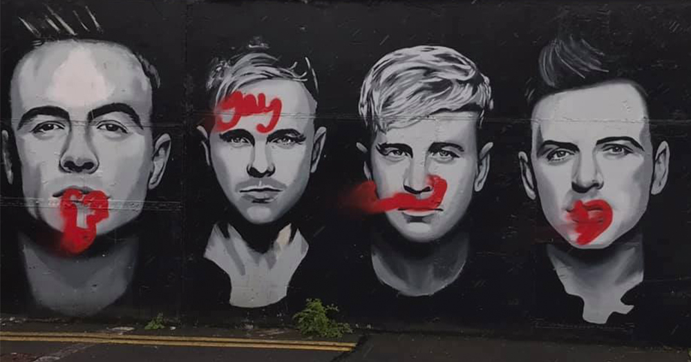 "black and white mural featuring 4 members of westlife with penis drawn on one band member's face and the word ""gay"" on another members."