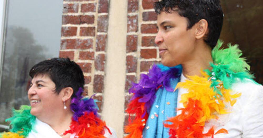 Cristina Palma and Mariama Dialo wearing rainbow coloured feather boa.