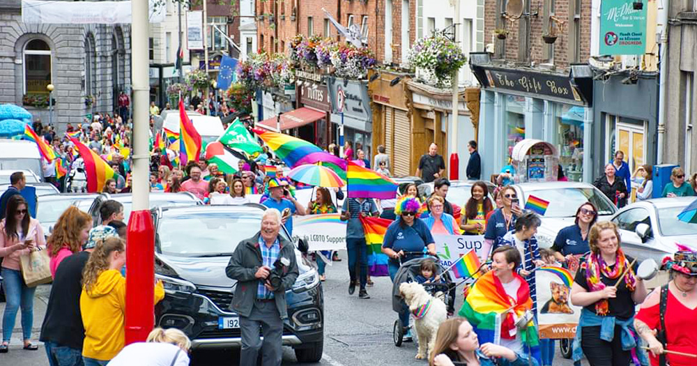 A Pride parade makes its way through an Irish village, people carrying a huge rainbow flag.
