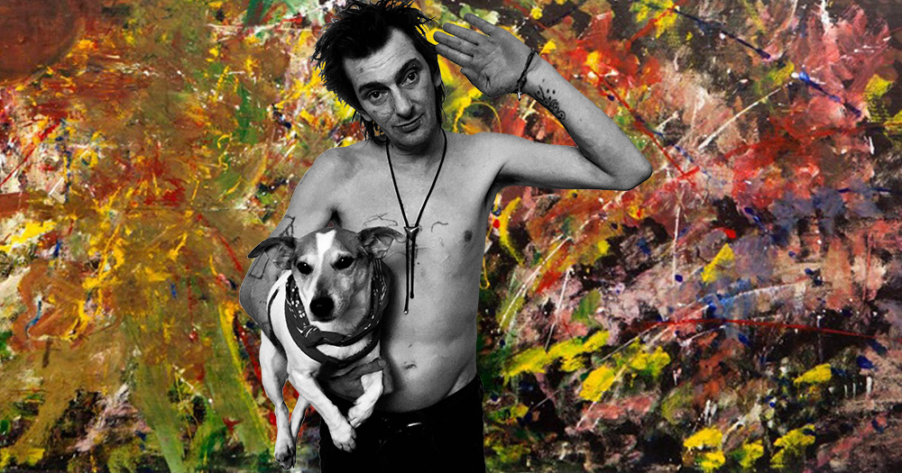 Christopher Main with his dog standing in front of one of his paintings