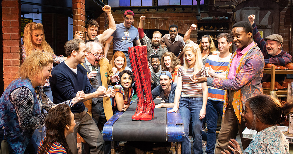 The cast of Kinky Boots gathered around a pair of boots in a factory