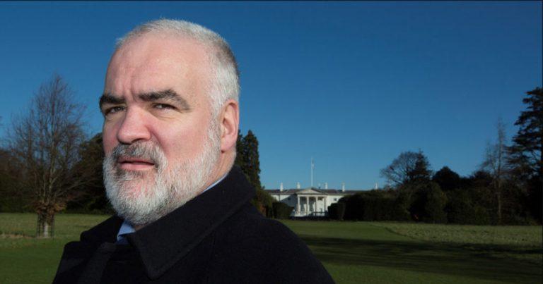 A bearded Noel Whelan with Áras an Uachtaráin in the background