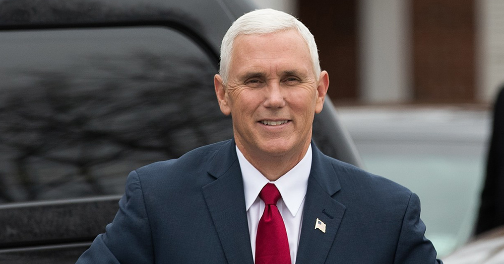 Mike Pence dressed in a suit smiling as he gets out of a car