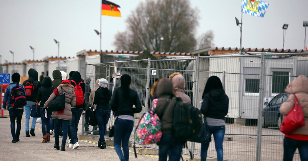 A line of asylum seekers walking by a fence
