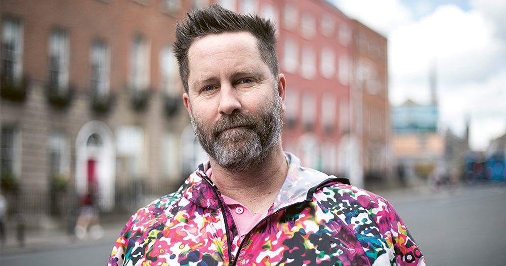 A man in a multicoloured hoodie stands on a street in Dublin