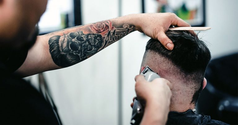 A person seen from behind getting their haircut in a barbershop