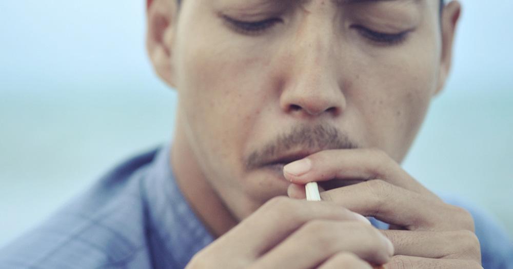 A man lighting a cigarette, part of Samak Kosem's photograph series.