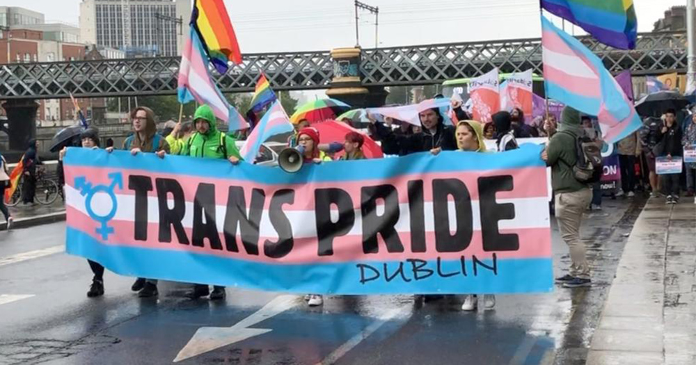 People holding a huge Trans Pride Dublin banner walking down a main street on a rainy day
