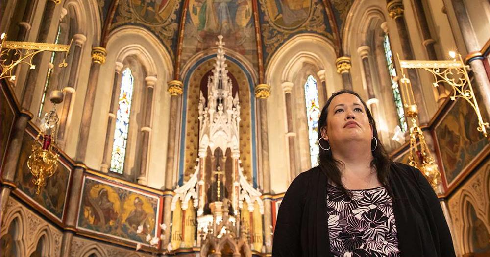 Alisha Cacase transgender Catholic Priest stands in church