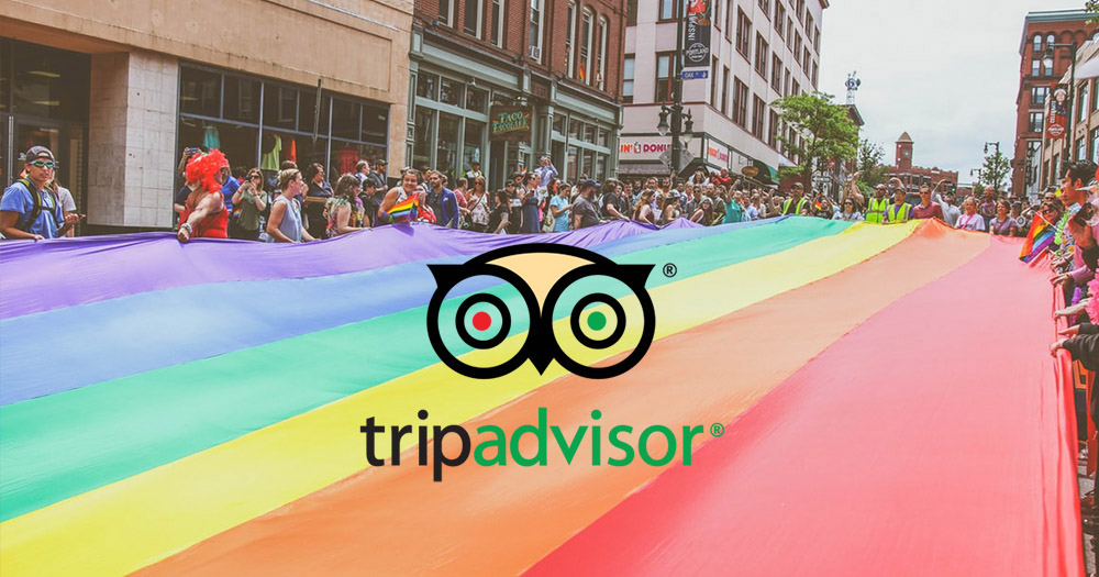 TripAdvisor logo in front of rainbow flag carried by crowd