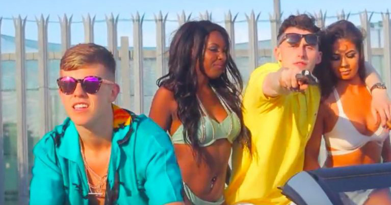 Versatile duo sit with two young women on a warm day, with Eskimo Supreme pointing a gun at the camera, in the music video for 'Dublin City G's'