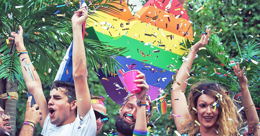 People celebrating Cork Pride with confetti and a rainbow heart.