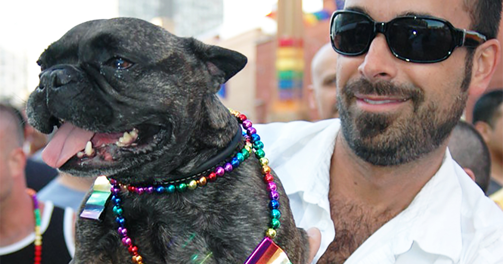 A man wearing sunglasses holds his dog wearing rainbow beads. This is one of the many dogs marching at Pride events around the world
