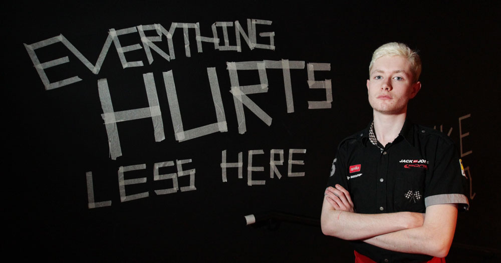 "person from National Youth Theatre stands in front of sign reading ""everything hurts less here"""