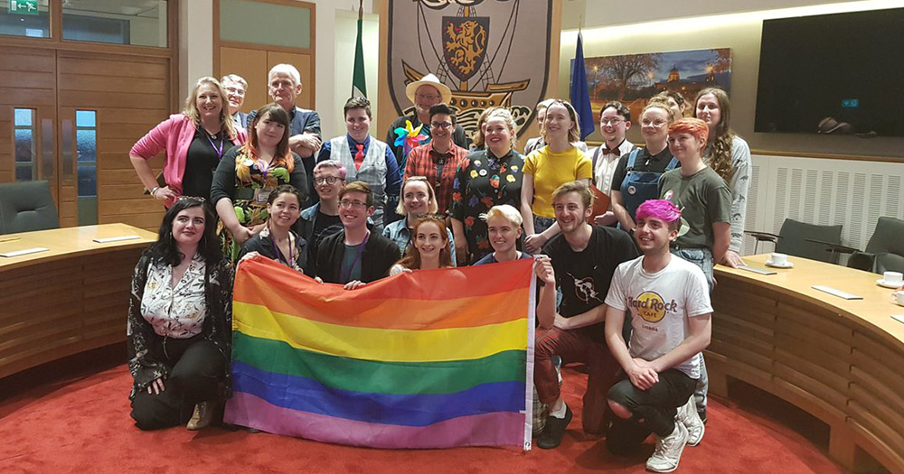 Councillor Owen Hanley holding a rainbow flag with the Galway Pride committee, AMACH! LGBT+ board, and the wider community.