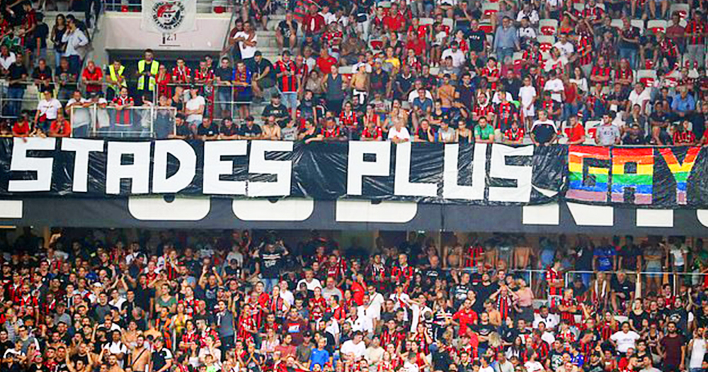 The stands of a French football match with fans unfurling a homophobic banner