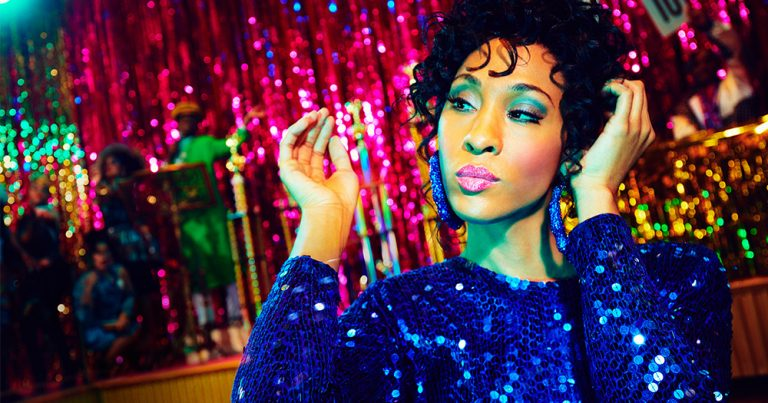 MJ Rodriguez posing in front of a stage wearing a sparking blue dress