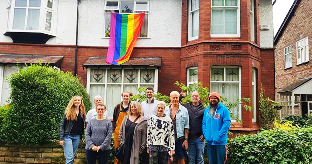 A group of neighbours stand outside a house with a rainbow flag hanging from the upstairs window