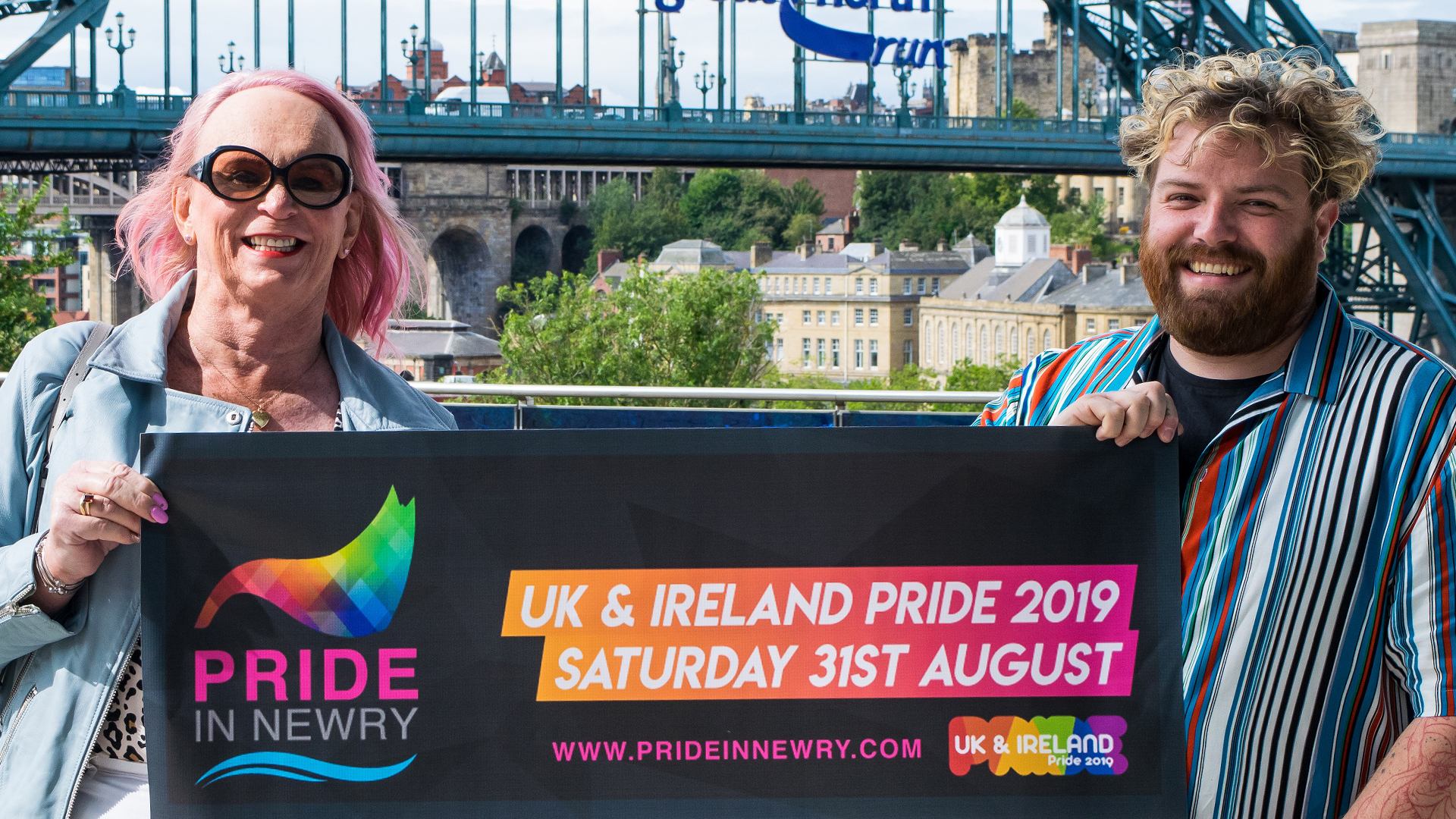 "Newcastle Pride team members stand behind a banner which reads ""Newry Pride"""