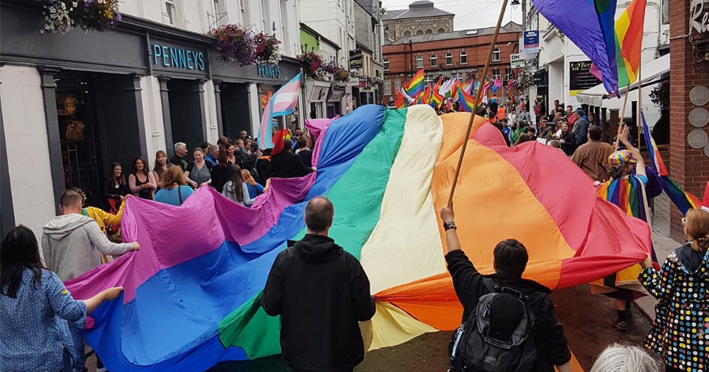 A huge rainbow flag fills Sligo Main Street, held aloft by crowds of people