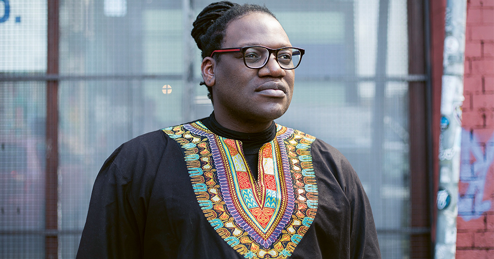 Niki Dube, a black man wearing glasses with his hair pulled back looking into the distance