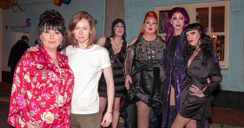Two women posing, behind them drag acts who performed in Tralee