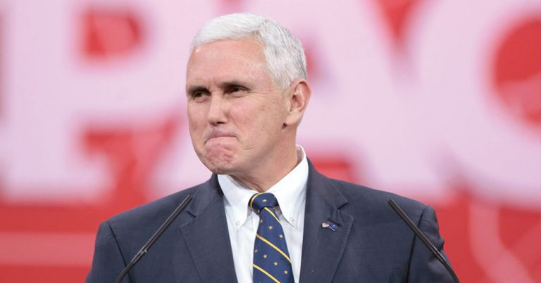 Mike Pence looking bitter in front of red backdrop.