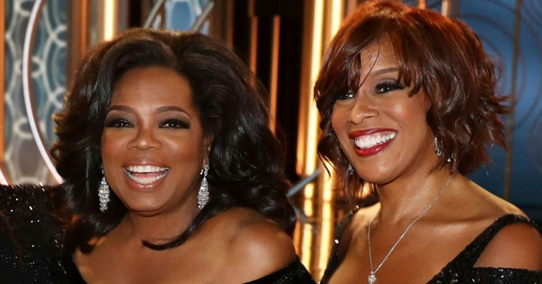 Oprah Winfrey and Gayle King both wearing black dresses and smiling at an event.