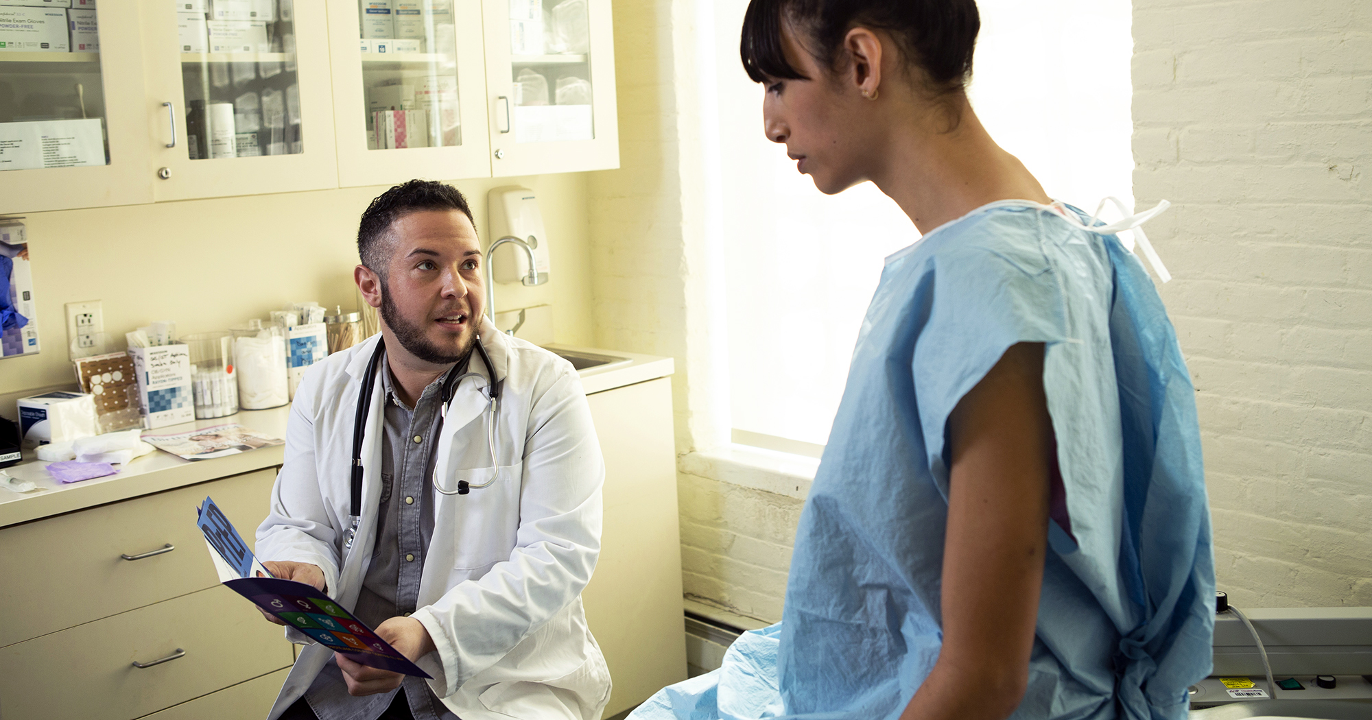 Doctor talking to patient wearing a hospital gown sitting on a bed. A new study on trans healthcare has been launched.