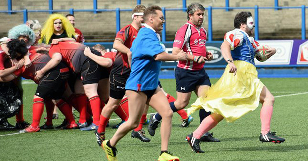 Men running during a rugby match. One of them is wearing a Snowhite outfit. An image of the match between Driff Drag and Cardiff Lions RFC