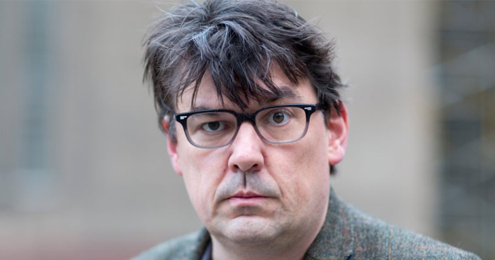 Graham Linehan with disheveled hair wearing glasses