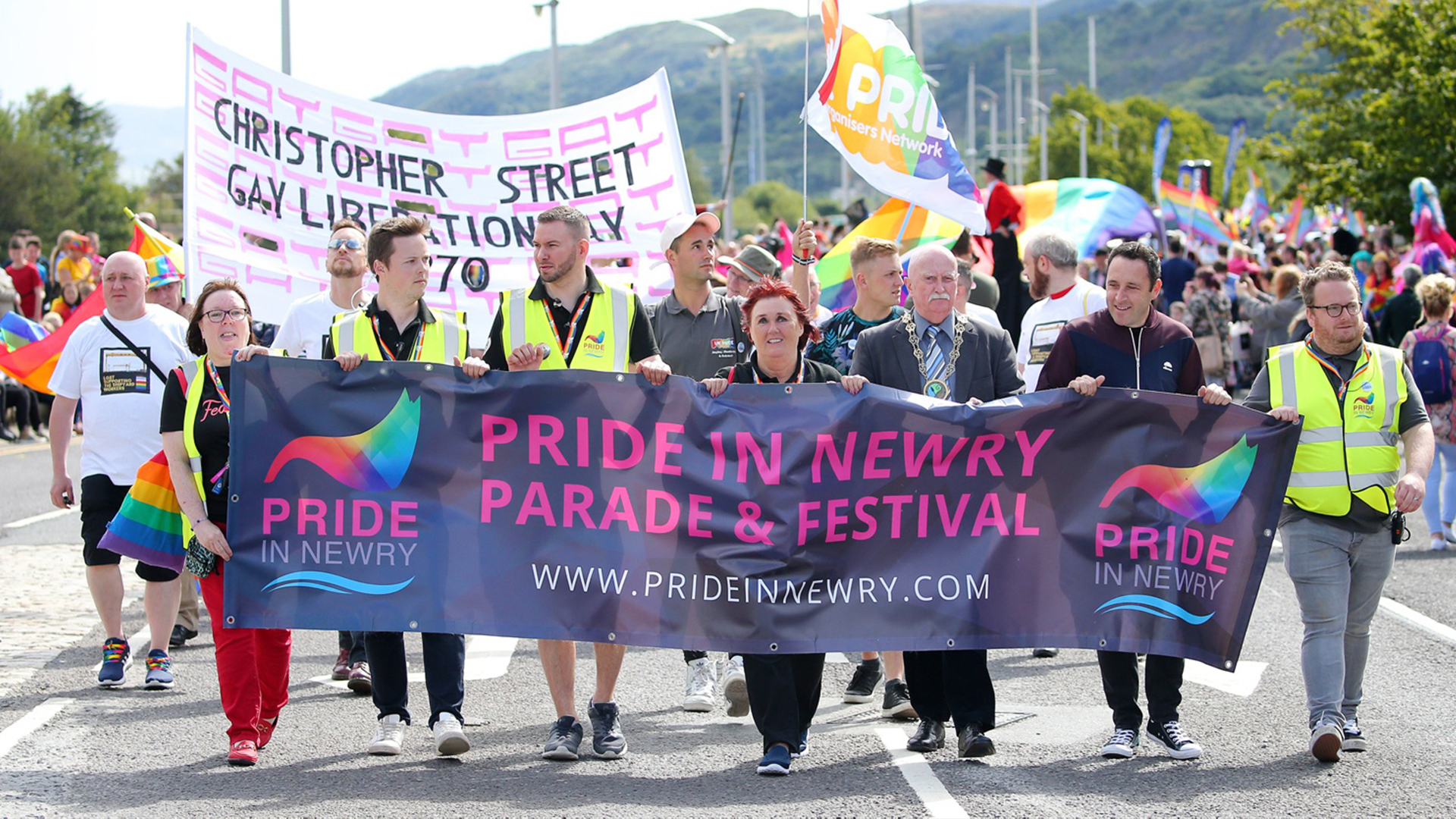 Newry Pride festival organisers walking in parade holding a banner which reads
