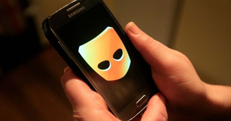 Close up of two hands holding a Samsung phone with the Grindr logo, a yellow mask with black eyeholes, coming up on the screen. A teenage boy was kidnapped after he met someone on the dating app.