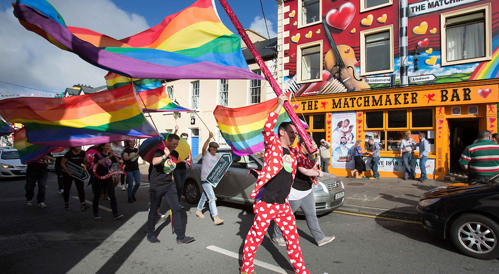A number of people dressed in brightly coloured clothes are walking down a road waving rainbow flags. They are walking past a pub called tThe Matchmaker which has a yellow sign and is adorned with red hearts.