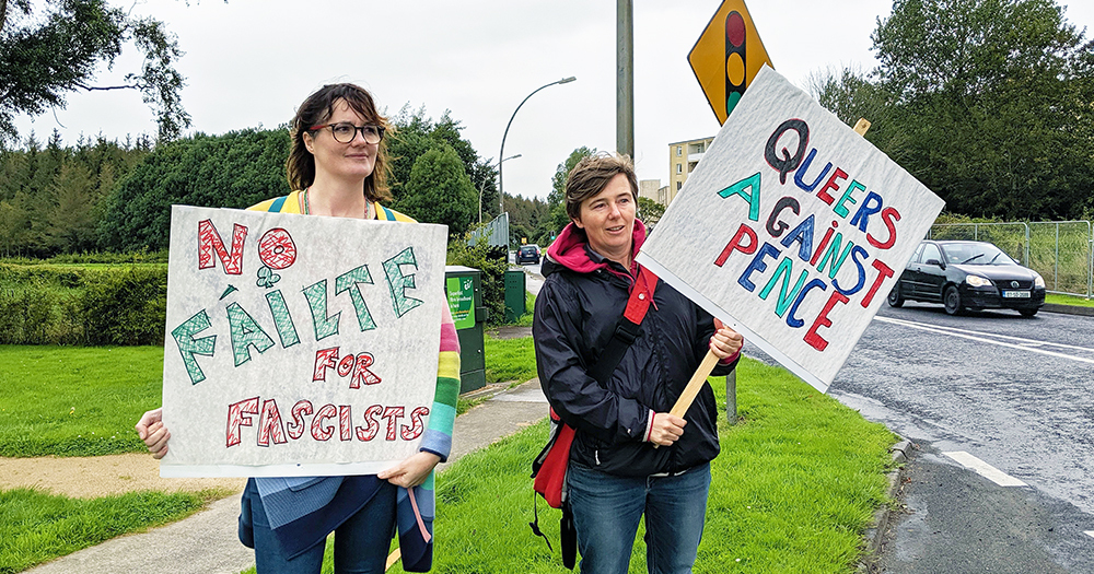 "Queer Irish poet, Sarah Clancy, is joined by another protestor as they hold signs reading ""No fáilte for fascists"" and ""Queers against Pence"" outside of Shannon Airport."