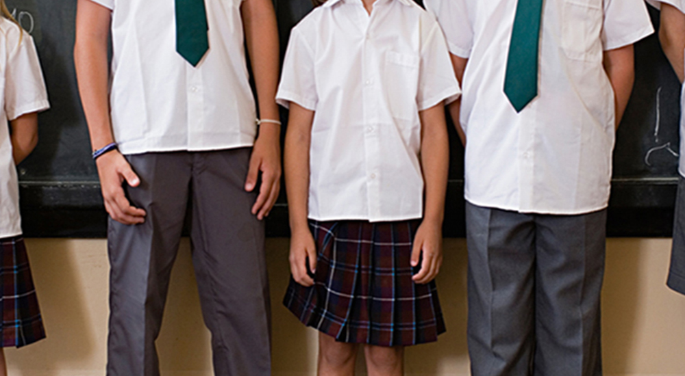 Children stand in front of black board in school uniforms