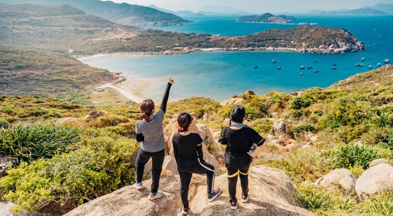Three women standing on top of a mountain overlooking scenic lake, QuestionMark recently conducted a survey on LGBT+ travelling.