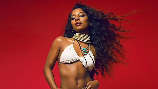 American singer-songwriter Victoria Monét against a red back drop
