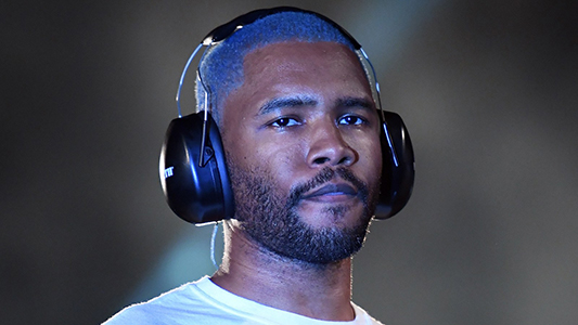 Frank Ocean wearing a white t-shirt and headphones. Ocean is one of the most revolutionary singers of his day.